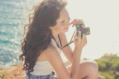 Ragazza turistica che fa foto dalla vecchia macchina fotografica sulla cima della montagna immagine stock