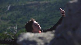 Ragazza turistica che prende foto con lo smartphone sopra le montagne archivi video