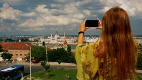 Ragazza turistica che prende le foto alla costruzione del Parlamento di Budapest stock footage