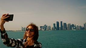 Ragazza turistica che prende le foto del selfie ai grattacieli con lo smartphone a Doha archivi video