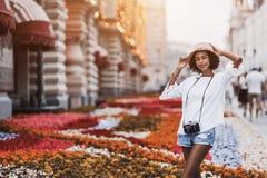 Ragazza turistica nera in cappello all'aperto con la macchina fotografica d'annata della foto Immagine Stock Libera da Diritti