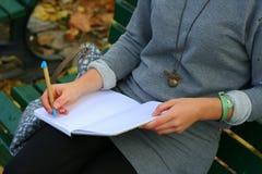 Ragazza in ubicazione grigia del vestito sulle note di scrittura del banco nel suo blocco note Immagini Stock Libere da Diritti
