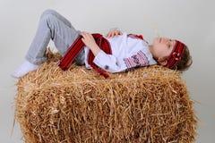 Ragazza ucraina in vestito e jeans nazionali che dorme nel fieno Fotografia Stock