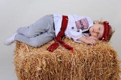 Ragazza ucraina in vestito e jeans nazionali che dorme nel fieno Immagine Stock