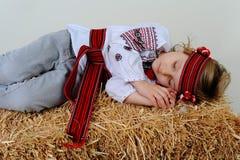 Ragazza ucraina in vestito e jeans nazionali che dorme nel fieno Fotografia Stock Libera da Diritti
