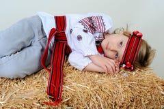 Ragazza ucraina in vestito nazionale e jeans che si trovano nella mangiatoia Immagini Stock