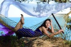 Ragazza in un'amaca su una costa tropicale fotografia stock libera da diritti