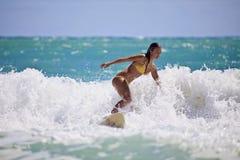 Ragazza in un bikini giallo che pratica il surfing Fotografie Stock