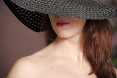 Ragazza in un black hat Fotografia Stock