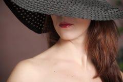 Ragazza in un black hat Fotografia Stock