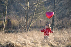 Ragazza in un campo che tiene pallone in forma di cuore Immagine Stock