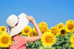 Ragazza in un cappello in un campo dei girasoli di estate La vista dalla parte posteriore Paesaggio floreale Immagine Stock Libera da Diritti