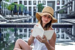 Ragazza in un cappello che legge un libro dallo stagno fotografia stock libera da diritti