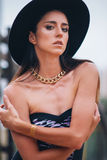 Ragazza in un cappello con il tatuaggio istantaneo metallico temporaneo sul suo braccio fotografia stock