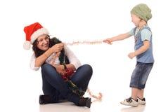 Ragazza in un cappello della Santa che gioca con un ragazzo Fotografia Stock