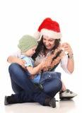 Ragazza in un cappello della Santa che gioca con un ragazzo Fotografia Stock Libera da Diritti