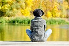 Ragazza in un cappello ed in un cappotto che si siedono sul bacino Autunno, soleggiato Vista posteriore immagini stock