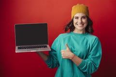 Ragazza in un cappello giallo con un computer portatile fotografie stock libere da diritti