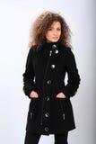 Ragazza in un cappotto nero immagine stock