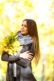Ragazza in un cappotto nero su un fondo dell'autunno con le foglie fotografia stock libera da diritti