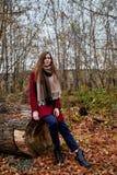 Ragazza in un cappotto rosso nel parco in autunno tardo immagine stock