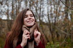 Ragazza in un cappotto rosso nel parco in autunno tardo fotografia stock