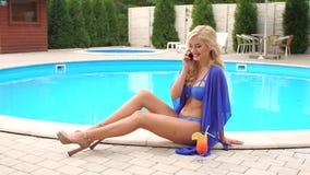 Ragazza in un costume da bagno che parla sul telefono vicino allo stagno stock footage