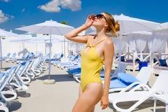 Ragazza in un costume da bagno dallo stagno nel resto del sole di estate fotografia stock