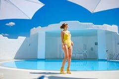 Ragazza in un costume da bagno dallo stagno nel resto del sole di estate immagine stock libera da diritti
