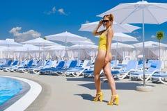 Ragazza in un costume da bagno dallo stagno nel resto del sole di estate immagini stock libere da diritti