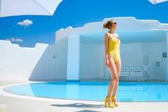Ragazza in un costume da bagno dallo stagno nel resto del sole di estate fotografia stock libera da diritti
