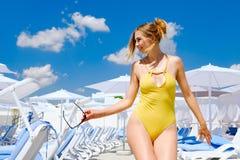 Ragazza in un costume da bagno dallo stagno nel resto del sole di estate fotografie stock