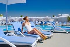 Ragazza in un costume da bagno dallo stagno nel resto del sole di estate fotografie stock libere da diritti