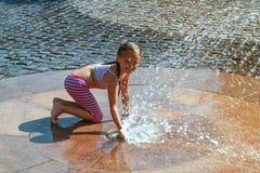Ragazza un giorno caldo soleggiato che gioca fuori in una fontana Ragazza felicemente in acqua pulita bassa sopra della fontana d fotografia stock libera da diritti