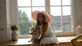 Ragazza in un grande cappello di paglia ed in una seduta bianca del vestito stock footage