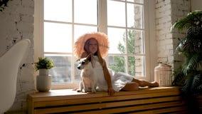 Ragazza in un grande cappello di paglia ed in una seduta bianca del vestito video d archivio