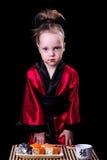 Ragazza in un kimono rosso prima di un piatto con i rotoli Fotografie Stock