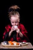 Ragazza in un kimono rosso prima di un piatto con i rotoli Immagini Stock