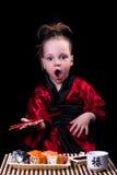 Ragazza in un kimono rosso prima di un piatto con i rotoli Immagine Stock
