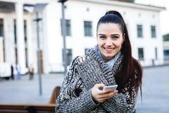 Ragazza in un maglione con un telefono sulla via Immagini Stock Libere da Diritti
