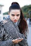 Ragazza in un maglione con un telefono sulla via Fotografia Stock Libera da Diritti