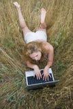 Ragazza in un pavimento con il computer portatile Fotografie Stock