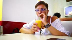 Ragazza in un succo bevente del caffè ed esaminare smartphone stock footage