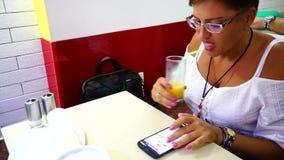 Ragazza in un succo bevente del caffè ed esaminare smartphone archivi video