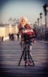 Ragazza in un supporto rosa del berretto vicino alla macchina fotografica su un supporto Fotografia Stock