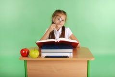 Ragazza in un uniforme scolastico che si siede ad uno scrittorio con una lente d'ingrandimento Immagini Stock Libere da Diritti