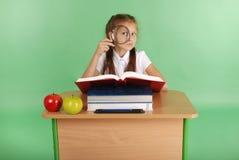 Ragazza in un uniforme scolastico che si siede ad uno scrittorio con una lente d'ingrandimento Fotografie Stock