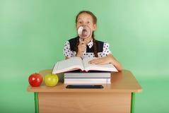 Ragazza in un uniforme scolastico che si siede ad uno scrittorio con una lente d'ingrandimento Fotografia Stock