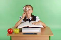 Ragazza in un uniforme scolastico che si siede ad uno scrittorio con una lente d'ingrandimento Immagine Stock Libera da Diritti