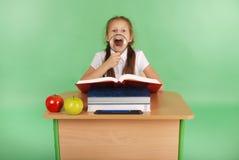 Ragazza in un uniforme scolastico che si siede ad uno scrittorio con una lente d'ingrandimento Fotografia Stock Libera da Diritti